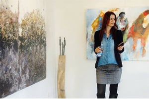 Woman standing in art gallery surrounded by paintings